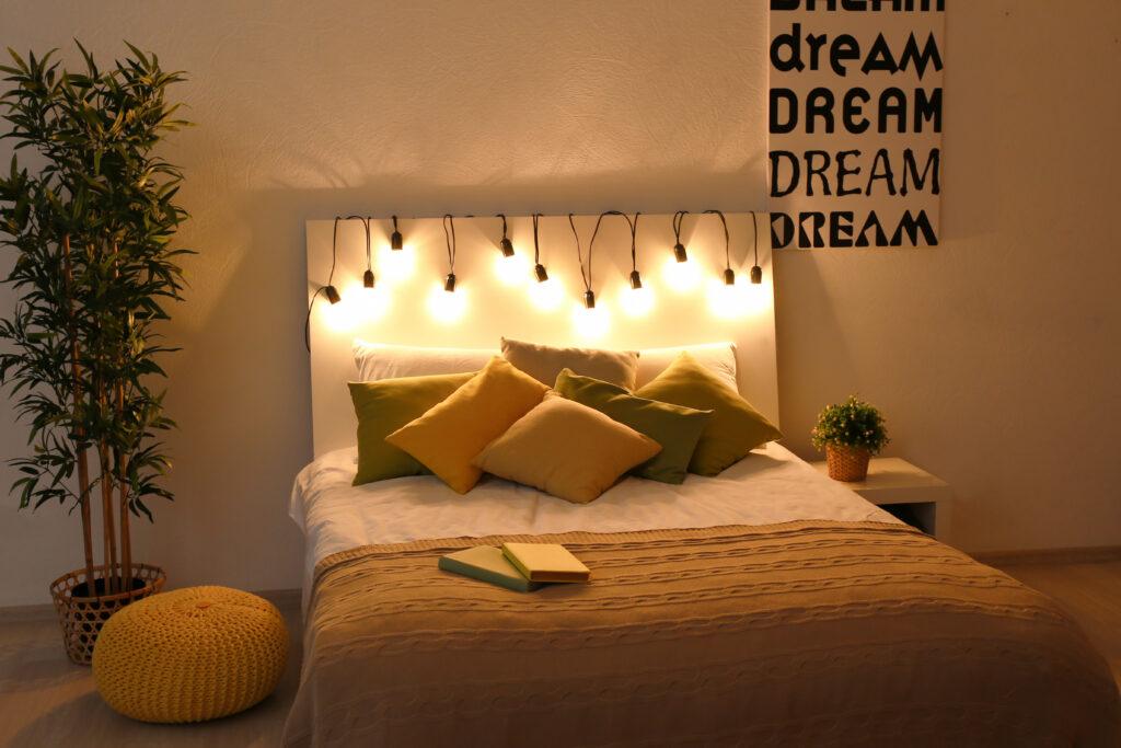 ein gemütlich dekoriertes Bett mit Licht einer Lichterkette, ausgeschlafen startest Du noch besser in Deine ayurvedische Morgenroutine