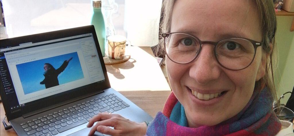 Bernadette sitzt an ihrem Schreibtisch und strahlt glücklich in die Kamera, weil sie gerade an einem Blogartikel schreibt.