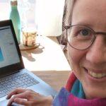 Bernadette sitzt an ihrem Arbeitsplatz, einem Hochtisch mit Laptop und warmem Wasser