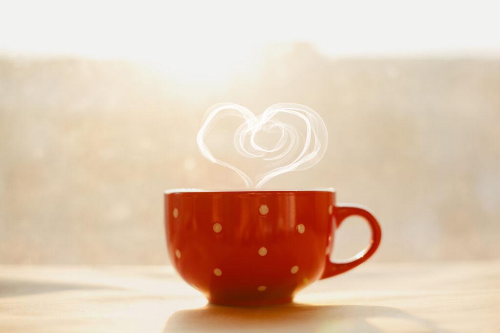 eine rote Tasse mit gelben Punkten, aus der Dampf in Herzform emporsteigt