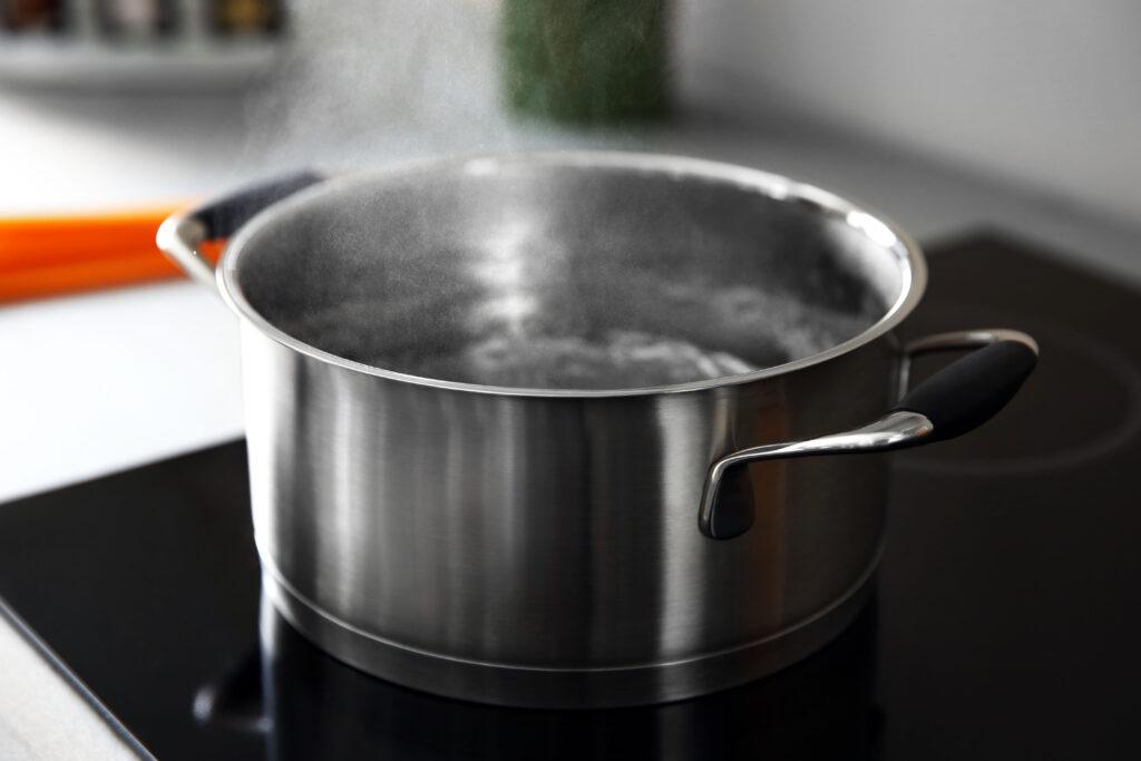 ein Edelstahltopf auf dem Herd mit kochendem Wasser, das warme Wasser hat in der ayurvedischen Morgenroutine einen hohen Stellenwert