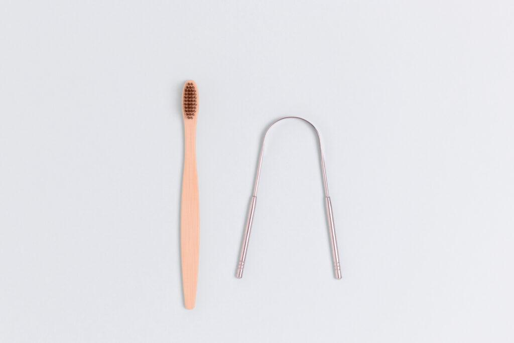 eine Zahnbürste aus Holz und ein Zungenschaber, unabdingbar in der ayurvedischen Morgenroutine