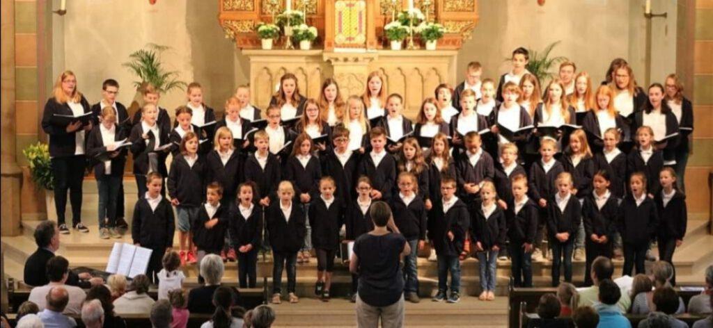 Kinder und Jugendliche vor einem Altar in Chorformation stehend, Bernadette als Dirigentin davor