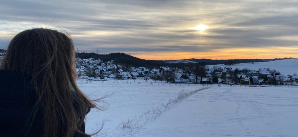 ich sitze mit dem Rücken zur Kamera und schaue in den Sonnenuntergang.